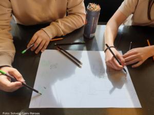 To personer tegner på et stort hvitt ark.