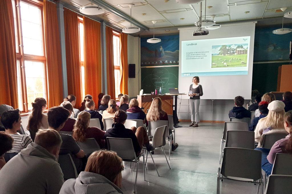 Bilde av at Spire holder foredrag under et skolebesøk ved Hardanger folkehøyskole i 2019. Foredraget er i en oppholdsrom, elevene sitter på grå stoler og på lerretet vises et powerpoint-slide om landbruk. Foto: Solveig Gjørv Røraas